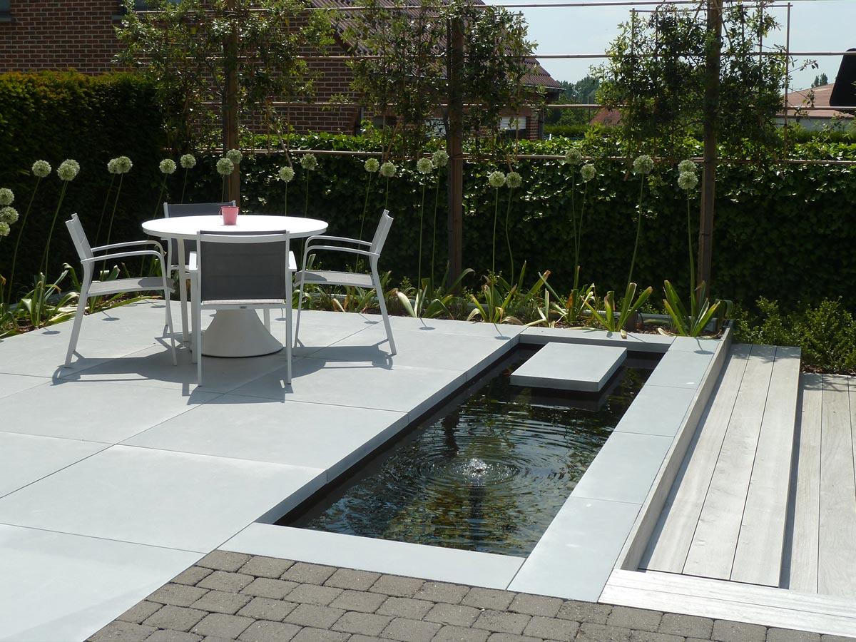 Modern terras met houten zitbanken in grote tegels en padouk for Moderne waterpartijen tuin